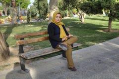 年轻回教妇女单独坐长凳在公园,伊朗 免版税库存照片