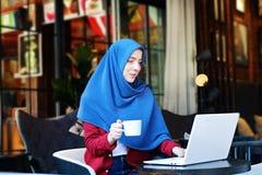 年轻回教妇女在熟悉内情的咖啡地方 免版税图库摄影