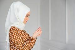 年轻回教妇女画象白色hijab和传统礼服祈祷的 库存照片