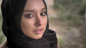 年轻回教妇女画象看与哀伤的沮丧的表示的hijab的照相机在雨期间 影视素材