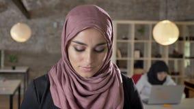 年轻回教妇女画象看在照相机的hijab的和下来,两名迷人的妇女的工作在现代办公室 股票视频