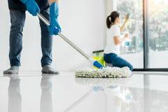 年轻围攻管家清洗的地板拿着拖把和塑料桶有刷子的,手套和洗涤剂在离开的屋子 免版税图库摄影