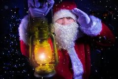 年轻圣诞老人,运载的灯笼神色通过雪与圣诞树和街灯blizard在背景中 库存照片