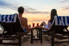 年轻在一个海滩的夫妇饮用的鸡尾酒在日落在假期时 免版税库存照片