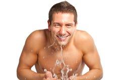 年轻在他的表面的人喷洒的水在刮以后在卫生间里 免版税库存照片