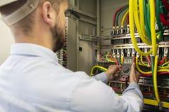 年轻在保险丝板的电工测量的电压 审查与多用电表探针的男性技术员Fusebox 免版税库存图片