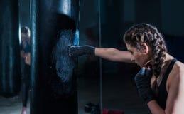 年轻在健身房的战斗机拳击手适合的女孩打的沙袋 妇女 免版税库存照片