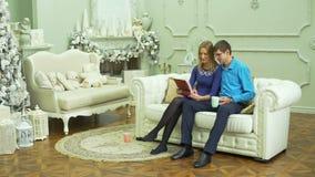 年轻在圣诞节内部的夫妇观看的照片 影视素材