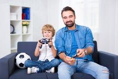 年轻在家打电子游戏的父亲和儿子 库存图片