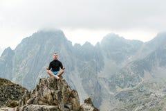 年轻在山顶部的人思考的瑜伽 概念旅行和和谐与自然 免版税库存图片