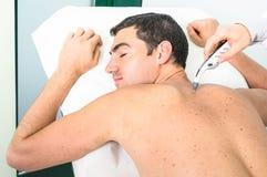 年轻在工作检查男性耐心皮肤的行家主要医生 免版税库存图片
