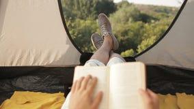 年轻在帐篷的人旅游阅读书在露营地在森林里 股票录像