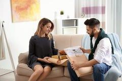 年轻在沙发的夫妇打开的小包在屋子里 免版税图库摄影