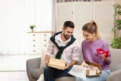 年轻在沙发的夫妇打开的小包 库存图片
