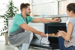 年轻在烤箱的夫妇烘烤的新月形面包 免版税库存照片