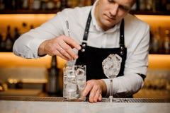 年轻在玻璃的男服务员活泼的冰块 免版税库存图片