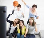 年轻在电视上的小组观看的体育 库存图片