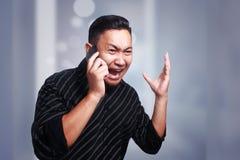 年轻在电话,震惊和哭泣的人恶化的新闻 免版税图库摄影