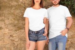 年轻在石墙附近的夫妇佩带的白色T恤杉 免版税库存照片