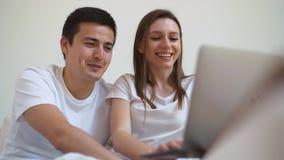 年轻在膝上型计算机的夫妇观看的录影画象在沙发在家 影视素材