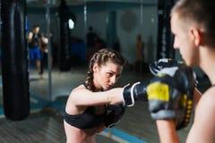 年轻在训练的战斗机拳击手适合的女孩佩带的拳击手套 免版税库存图片