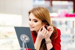年轻在金银手饰店的秀丽高雅妇女尝试的耳环 图库摄影