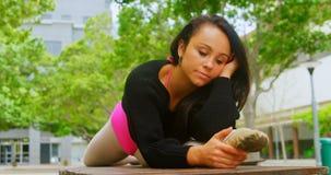 年轻在长凳的芭蕾舞女演员实践的芭蕾舞蹈在公园4k 股票录像