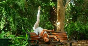 年轻在长凳的芭蕾舞女演员舞蹈家实践的舞蹈在公园4k 影视素材