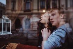 年轻在长沙发的夫妇抽烟的水烟筒 免版税库存图片