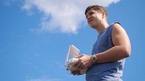 年轻在领域的人控制寄生虫 拿着在美好的天空背景的寄生虫操作员一台发射机 库存图片