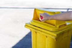 年轻在黄色容器的男孩手trow塑料瓶 图库摄影