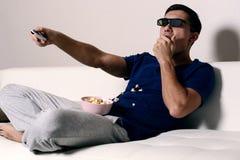 年轻在3D玻璃和吃玉米花的人观看的电影 库存照片