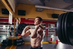 年轻在deadlift锻炼期间的人举的杠铃 库存照片
