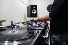 年轻在DJ控制器的人使用的和混合的音乐 库存照片