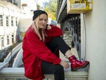 年轻坐在桥梁下的一件被编织的黑帽会议和红色夹克的行家白肤金发的女孩 免版税库存图片