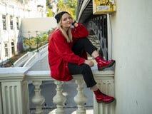 年轻坐在桥梁下的一件被编织的黑帽会议和红色夹克的行家白肤金发的女孩 库存照片