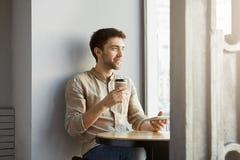 年轻坐在自助食堂的透视男性自由职业者的设计师画象,看在旁边满意对新的他的 免版税库存图片