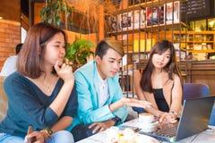 年轻坐在谈的事务的咖啡馆桌上的人和妇女w 免版税图库摄影