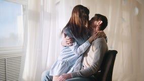 年轻坐由窗口的人和女孩在一间明亮地被点燃的屋子,拥抱和亲吻 影视素材
