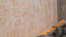 年轻大师在墙壁上把陶瓷砖放在屋子里 他在黏着性表面小心地安置长方形板材在宽敞 影视素材