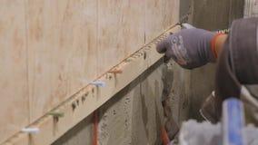 年轻大师在墙壁上把陶瓷砖放在屋子里 他在黏着性表面小心地安置长方形板材在宽敞 股票录像