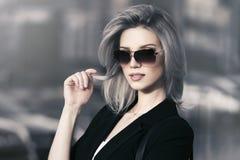 年轻太阳镜的时尚白肤金发的女商人走在城市街道的 库存图片