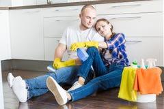 年轻夫妇丈夫和妻子做房子清洁 人和女孩洗涤有拖把和布料的厨房 库存图片