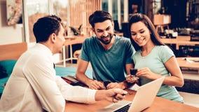 年轻夫妇与家具卖主协商 免版税库存照片