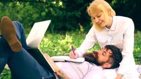年轻夫妇为检查做准备在公园 有胡子的说谎在有膝上型计算机的一条毯子的人和一个俏丽的女孩和 股票视频