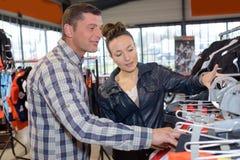 年轻夫妇买的夹克和礼服在精品店 免版税图库摄影