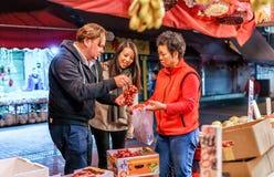 年轻夫妇买的果子在Tai Po的香港室外食物市场上 被停泊的晚上端口船视图 库存照片