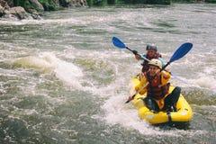 年轻夫妇享用划皮船在河的浪端的白色泡沫 库存图片