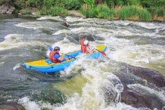 年轻夫妇享用划皮船在河的浪端的白色泡沫 库存照片