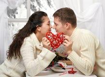 年轻夫妇亲吻和展示浪漫一个红色心脏、愉快的人-和爱概念 库存照片